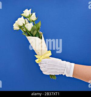 Hand in white-glove holds bouquet of white roses wrapped in tortilla on classic blue. Concept of edible, zero waste or eco-friendly gift wrapping - Stock Photo