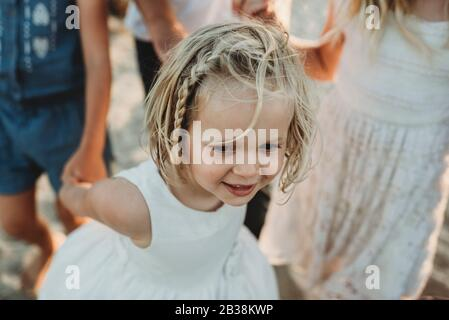 Young girl smiling and walking while holding sisters hands