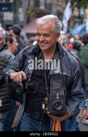 Man walking with an old camera at Popular manifestation the National Day Memory, Truth and Justice - Stock Photo