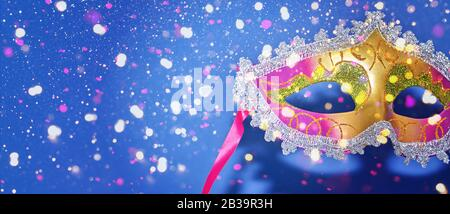 Venetian carnival Mardi Gras party. Bright festive decor. Mardi Gras masquerade mask on blue background with confetti. Invitation, banner, card, poster, flyer. - Stock Photo