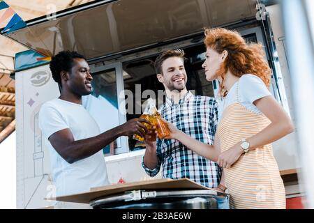 low angle view of happy multicultural men clinking bottles of beer with attractive redhead woman near food truck - Stock Photo