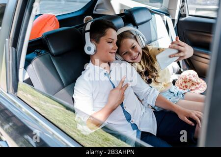 selective focus of happy sister taking selfie near brother showing peace sign in car - Stock Photo
