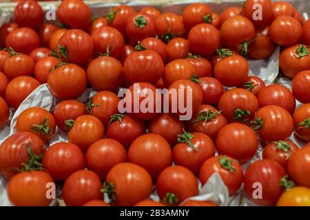 Small red cherry tomatoes with a leaf, top view. Pile of ripe red tomatoes in a crate in a supermarket. Fresh Vegetables Department at Grocery Store - Stock Photo