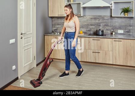 A young Caucasian woman vacuums a kitchen floor using a cordless vertical vacuum cleaner, or electric broom. The maid is cleaning up the hostels cook - Stock Photo