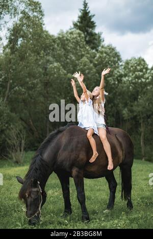 Two funny children girls sisters friends riding a horse together through a field. Girls sitting on a horse and holding arms up, happy outdoor walking
