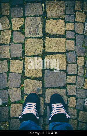 Top down view of feet in a pair of skater sneakers on a cobblestone pavement. Cobblestone patterned background. Minimalist urban style. - Stock Photo