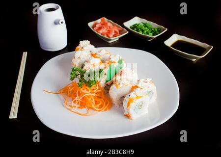 sushi rolls with Soy sauce on a black background