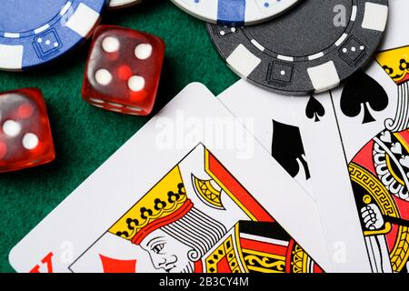 Poker chips, playing cards and dice on a green backgrorund. gambling - Stock Photo