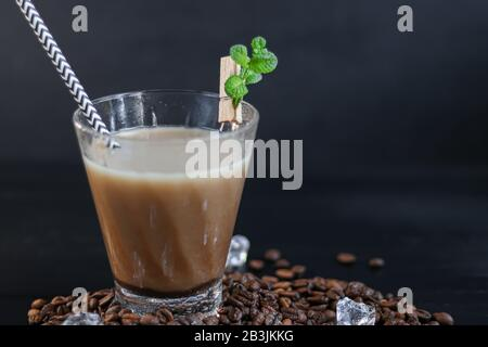 Iced coffee in a tall glass with milk and pieces of ice. On a dark background. Copy space - Stock Photo