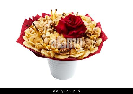 Large bouquet consisting of exotic dried fruits and nuts, decorated with a large red rose, stands in a vase. - Stock Photo