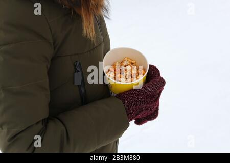 Young woman holding popcorn in winter, in mittens - Stock Photo