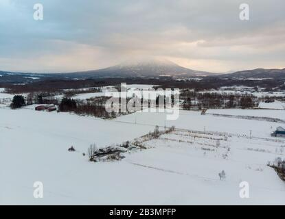 Winter morning landscape photo of snow covered fields and bare trees with the majestic volcanic mountains being lit up by the morning sun in the backg - Stock Photo