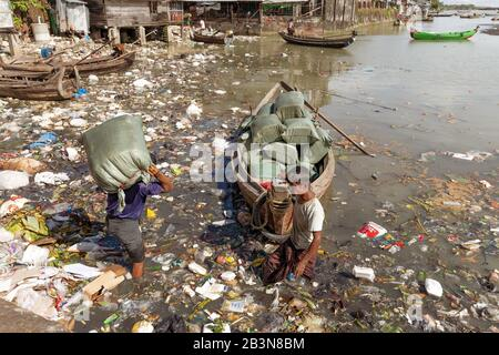 Two men unloading sacks of produce from a small boat in Sittwe harbour, wading through polluted water full of plastic rubbish, Sittwe, Rakhine, Myanma - Stock Photo