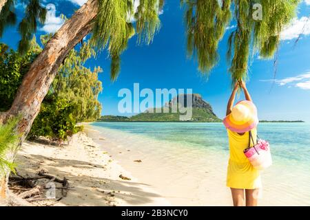 Woman having fun under a tropical tree on sandy beach, Ile aux Benitiers, La Gaulette, Le Morne Brabant, Mauritius, Indian Ocean, Africa