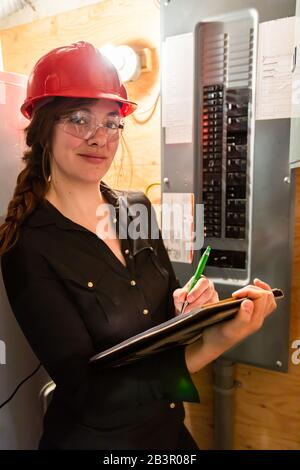 inspector woman inspects house electrical systems, she checks the Distribution board as she takes notes. inspecting a modern eco energy efficient home - Stock Photo