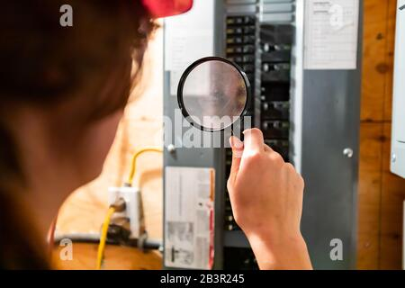 selective focus on inspector woman's hand holding a magnifying glass in the front of home Distribution panel board. house electrical systems check - Stock Photo