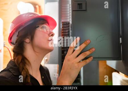 close up on construction inspector woman inspect house electrical systems, inspecting a modern eco energy efficient home. check the Distribution board - Stock Photo