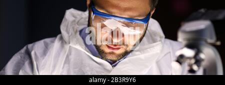 Man laboratory repairs instrument near microscope