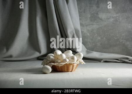 Still life with Easter eggs on a wooden table covered with a tablecloth with space for an advertising product. Cozy home interior.