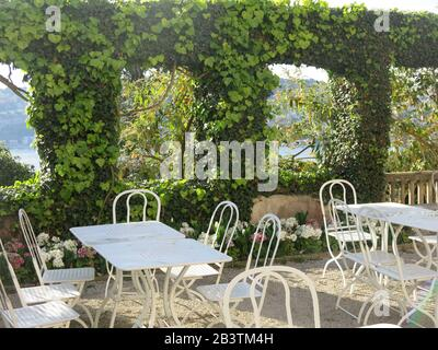 Table & chairs on a shady terrace in the grounds of the Villa Ephrussi de Rothschild, one of the French Riviera's spectacular gardens to visit. - Stock Photo