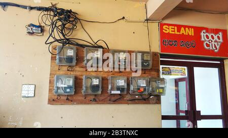 Old electricity meters are hanging on the wall. - Stock Photo