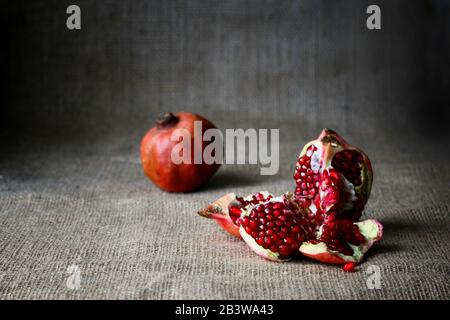 Red Half pomegranate and raw pomegranates on a brown sackcloth background. Rustic style. Tasty fruit, vitamin coctail Stock Photo