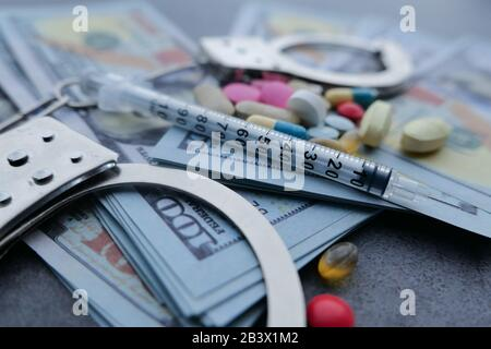 close up of pills , syringe and cash on on table - Stock Photo