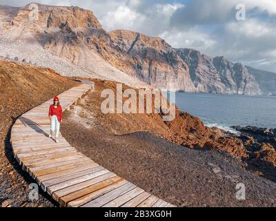 Woman walking on the picturesque wooden pathway through the rocky land with mountains on the background. Image made on mobile phone