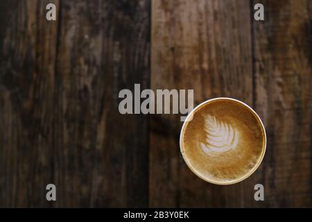 Coffee cup with decorative leaf design in on rustic wood background - top view with space for text - Stock Photo