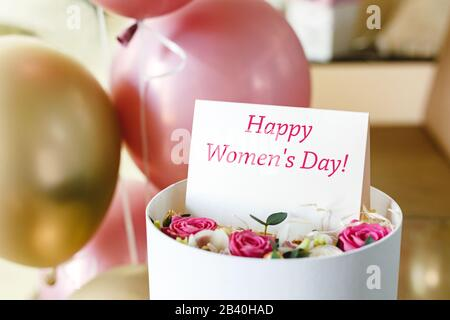 Happy Womens Day text on gift card in flower box near festive rose and gold balloons. Greeting card for women on 8 March, International Women's Day - Stock Photo