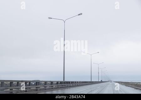 Dark highway in cloudy weather after rain.straight way with dramatic clouds. empty highway, cloudy sky, lighting on the road. Travel in any weather.