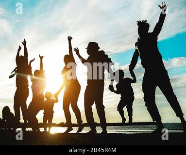 Silhouette of big family having fun on the beach at sunset - Father, mother, children and uncles enjoying time together - Focus on bodies - Love, rela