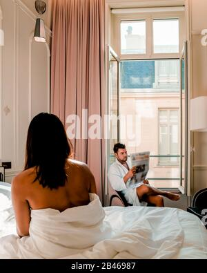 Morning wake up in bed in Paris with breakfast coffee and a newspaper, couple in bed men and woman honymoone valentine couple - Stock Photo