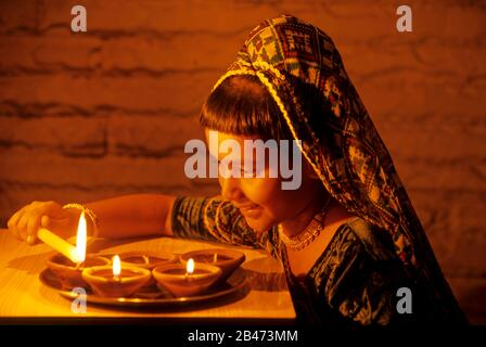 Girl lighting oil lamps on Diwali Festival, India, Asia, MR#201 - Stock Photo