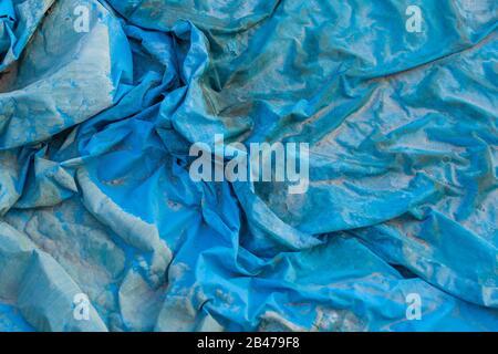 Closeup shot of a wrinkled blue plastic film texture