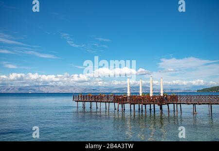 Long wooden pier with romantic cafe in end in Ionian sea. Greece. Beautiful lanscape, mountains on sealine. Sunny day with clouds on Corfu island. - Stock Photo