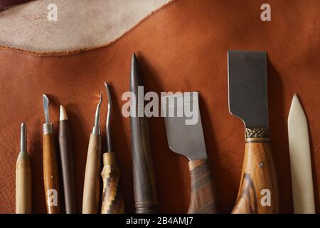 Horizontal from above flat lay shot of various tools for craftwork with leather materials lying on table in raw - Stock Photo