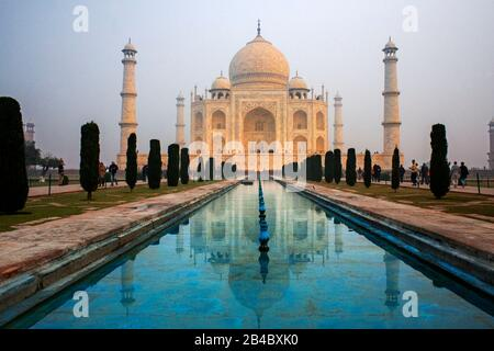 Taj Mahal tomb with reflection in the water at blue dramatic sky in Agra, Uttar Pradesh, India. This is one of the excursion of the Luxury train Mahar - Stock Photo