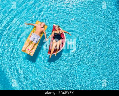 Above vertical view of people old senior couple taking hands with love and having fun on the blue clear swimming pool together enjoying the summer holiday vacation with trendy coloured lilos inflatable mattress - Stock Photo