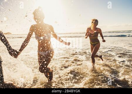 Funny summer vacation holiday group of young people playing and running in the sea waves on the shore - enjoying sunny day and outdoor leisure activity at the beach together - Stock Photo