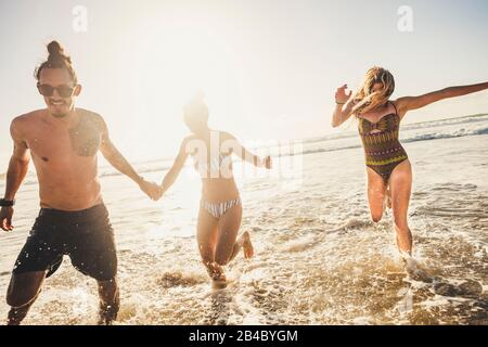 Group of young people friends enjoying with fun the summer holiday vacation running at the beach to the water in playful outdoor leisure activity together - youthful men and women - Stock Photo