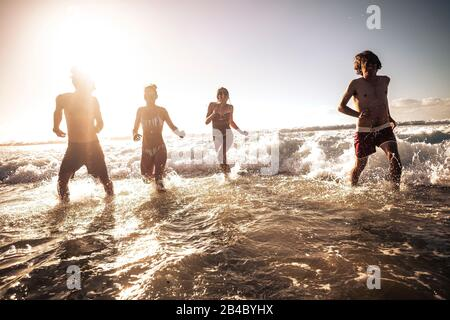 Group of happy young millennial people play and run in the sea waves water together - friends having fun in playful summer holiday vacation leisure activity - sunset and sunlight background - Stock Photo