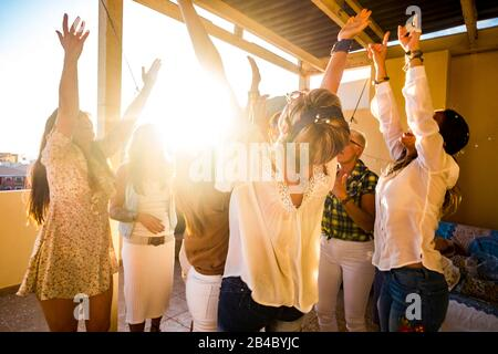 Active happy group of young free caucasian people woman celebrate and dance all together with friendship - sunset in backlight for party at home concept - Happiness for group - Stock Photo