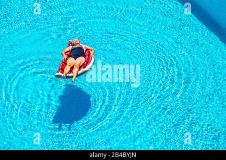 Senior aged lady sleep and relax enjoying the blue water of swimming pool lay down on red watermelon lilo - summer vibes and retired lifestyle for caucasian people - Stock Photo