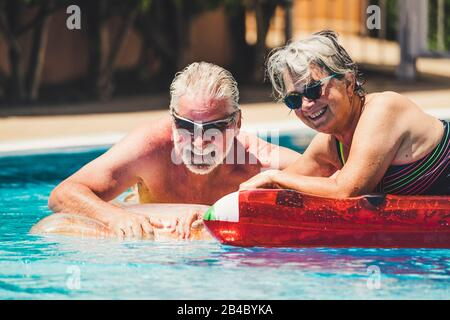 Happy joy cheerful people adult senior couple have fun in the swimming pool with trendy coloured lilos mattress on a blue water in hotel resort for summer holiday vacation lifestyle - Stock Photo