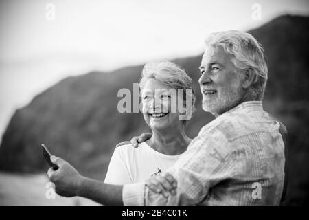 Beautiful romantic portrait of senior happy couple smile and hug eachother with love - forever together concept and active elderly happy lifestyle - white clear background and people smiling