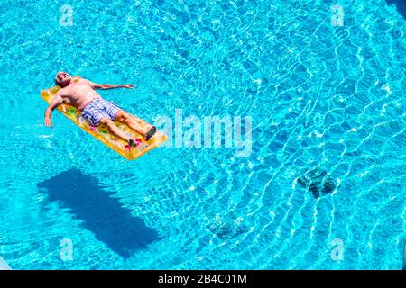 Senior aged man sleep and relax enjoying the blue water of swimming pool lay down on red watermelon lilo - summer vibes and retired lifestyle for caucasian people - Stock Photo
