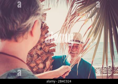 Old people senior caucasian couple man and woman playing and having fun together in outdoor leisure activity - happy retired youthful concept with cheerful male and female