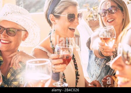 Closeup of happy beautiful cheerful people women celebrating together with red wine - bright sunny image joyful and friendship - young senior ladies smiling and laughing having fun at party - Stock Photo