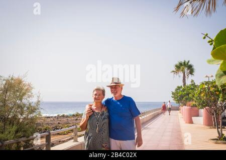 Happiness in retired lifestyle people with caucasian senior aged couple walking happy  hugging eachother with love - forever concept and enjoying outdoor leisure activity